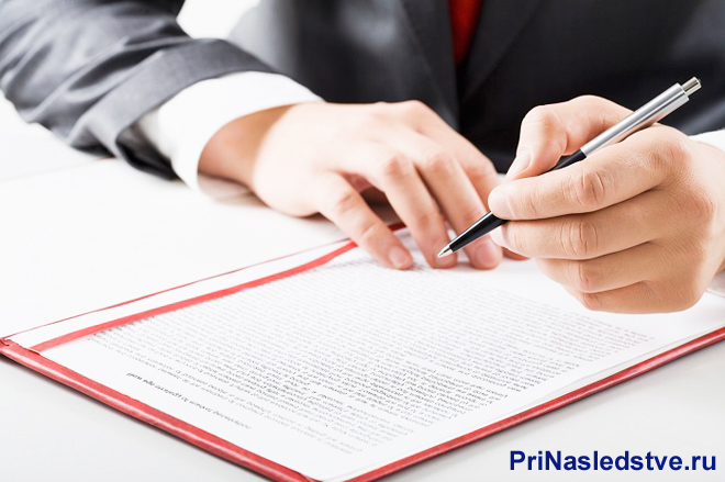 Бизнесмен подписывает документы в красной папке