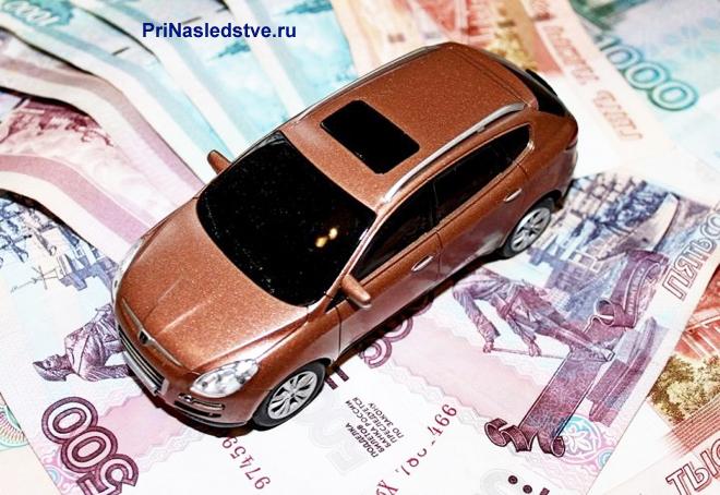 Коричневый автомобиль стоит на денежных купюрах