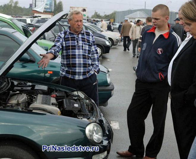 Мужчина показывает свой автомобиль покупателям