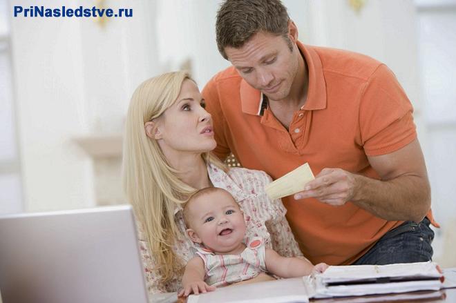 Семья с маленьким ребенком сидит около ноутбука
