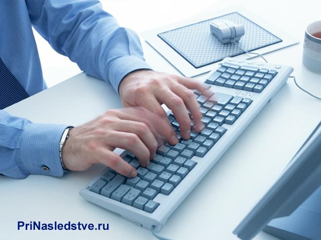 Мужчина в рубашке печатает на клавиатуре