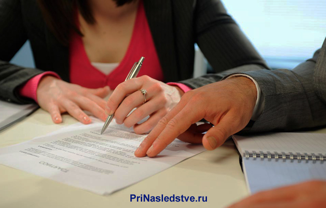 Девушка и мужчина подписывают документы за столом