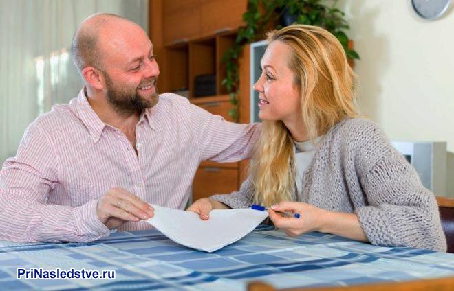 Муж и жена общаются за столом