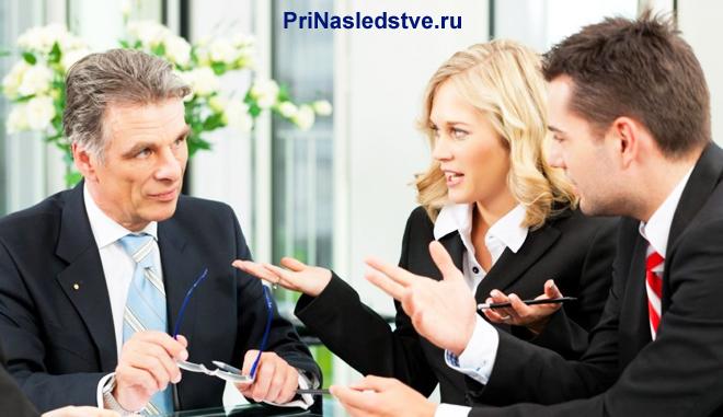 Двое мужчин и женщина общаются за столом переговоров