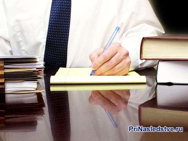 Мужчина в белой рубашке сидит за столом и подписывает документы, рядом лежат книги