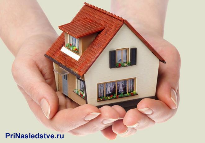 Девушка держит в руках домик с оранжевой крышей