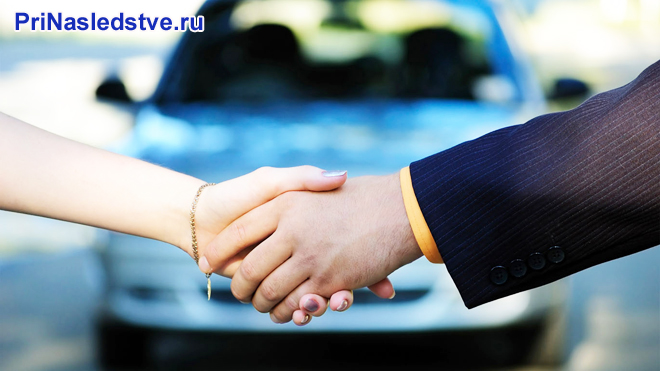 Женщина и мужчина жмут руки на фоне синего автомобиля
