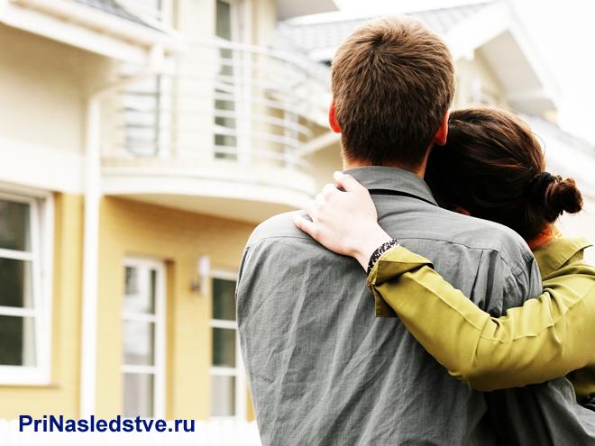 Молодая семейная пара смотрит на загородный дом