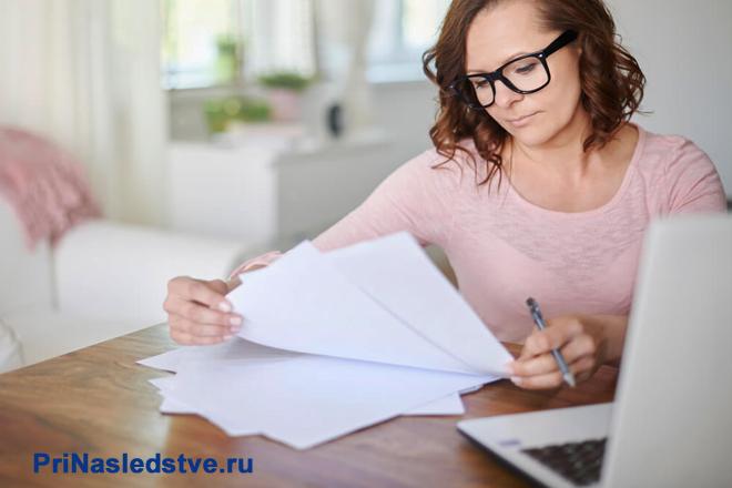 Девушка в розовой кофточке изучает бумаги за столом