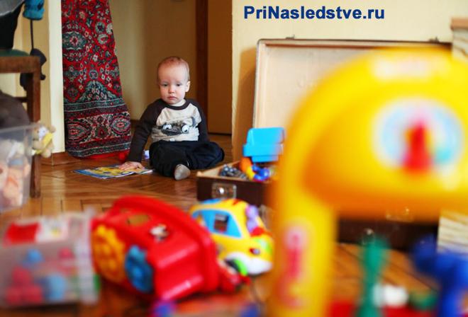 Мальчик играет в квартире с игрушками