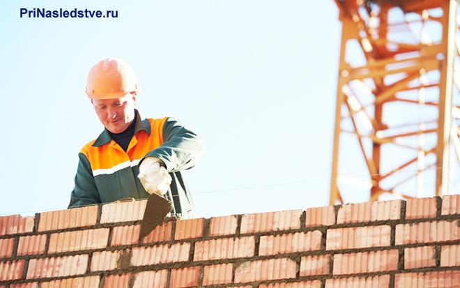 Строитель строит дом