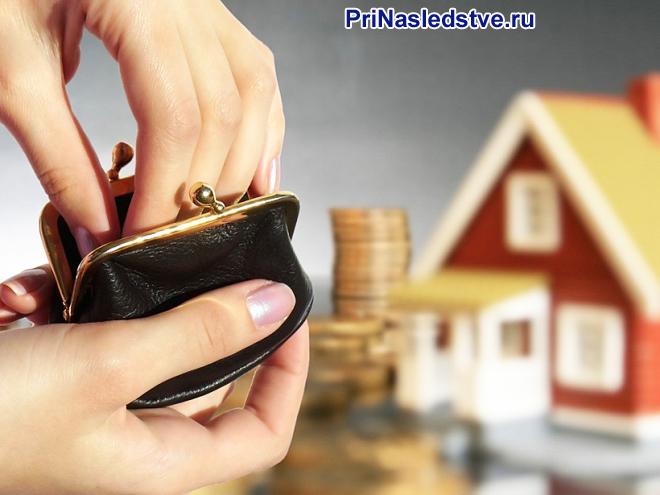 Девушка достает из кошелька монеты на фоне домика
