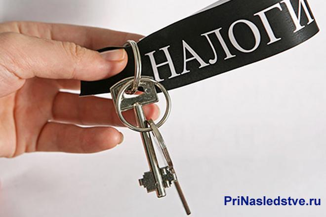 Человек держит ключи с ленточкой Налоги
