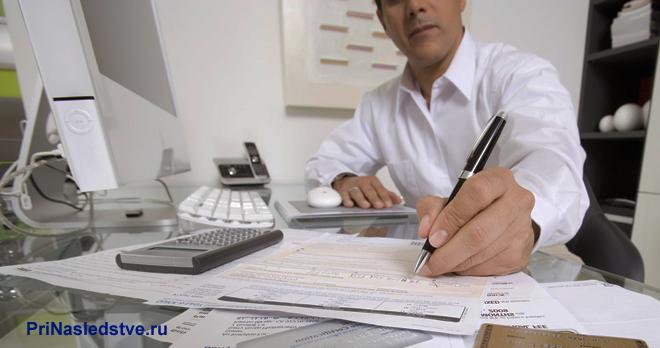 Мужчина в белой рубашке сидит за своим рабочим местом и оформляет документацию