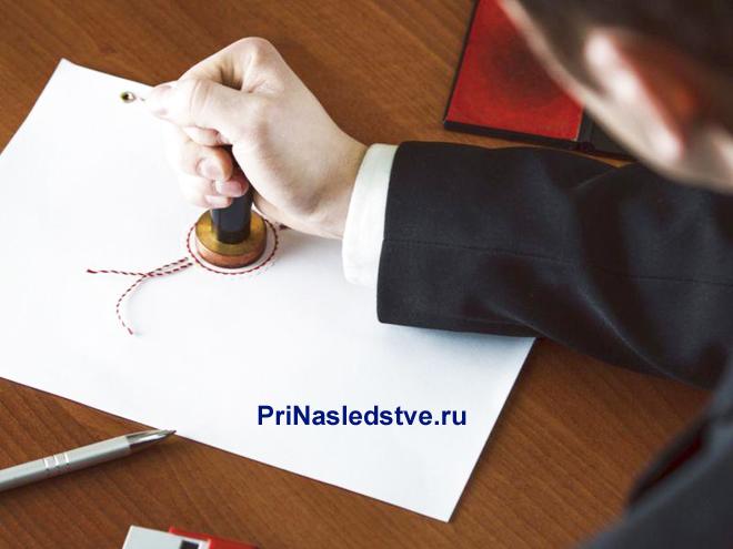 Мужчина в костюме ставит печать на листке бумаги