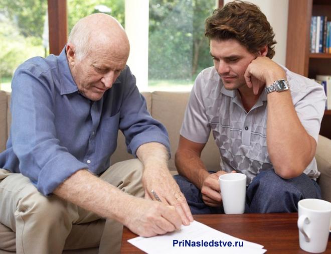 Двое мужчин сидят на диване и подписывают документы