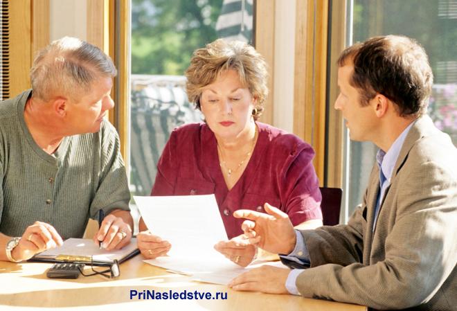 Двое мужчин и женщина сидят за столом и читают документацию