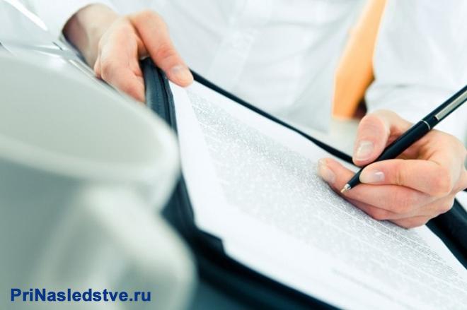 Бизнесмен в белой рубашке пишет ручкой на листке