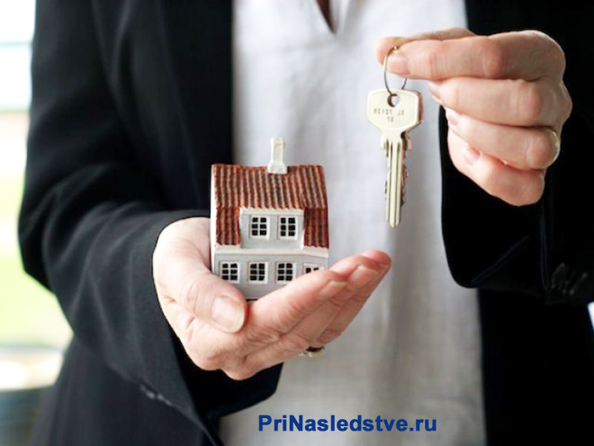 Мужчина держит в руках домик и ключи