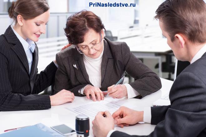Женщина подписывает документы, рядом с ней сидят работники офиса