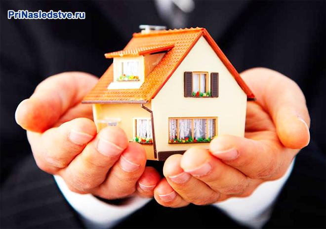 Бизнесмен держит на ладонях домик с рыжей крышей