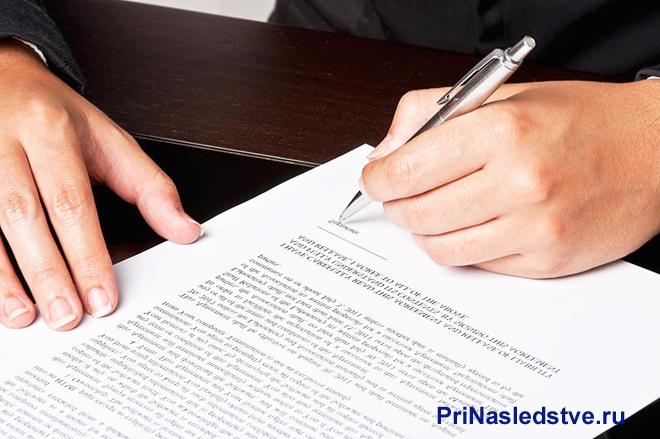 Мужчина ставит подпись на контракте