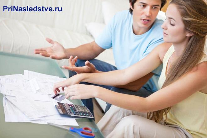 Семейная пара сидит на диване и считает на калькуляторе