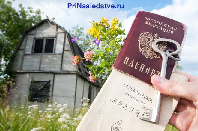 Человек держит в руке паспорт и документы на дачу