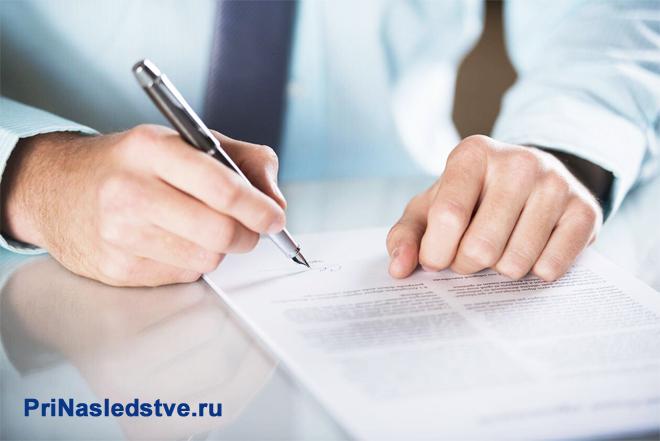 Мужчина в голубой рубашке ставит подпись на документе