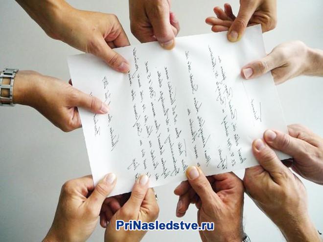Лист с рукописным текстом держат много рук