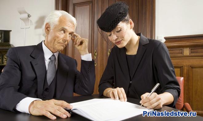 Женщина в темной одежде подписывает документ, рядом сидит мужчина