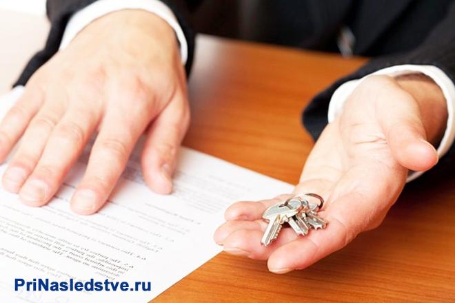Мужчина в деловом костюме сидит за столом, держит в руке ключи