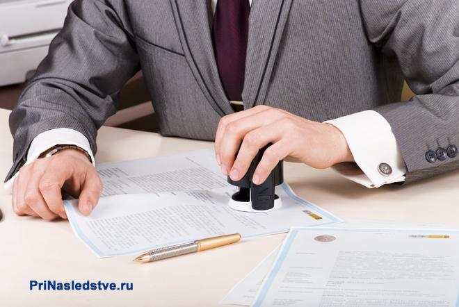 Мужчина в сером костюме ставит печать на документах