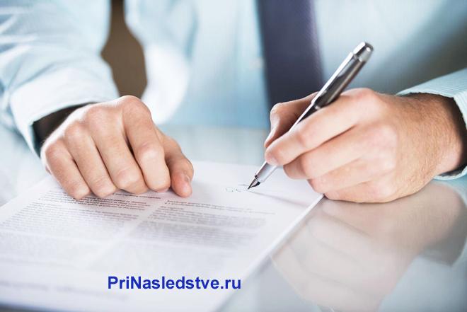Бизнесмен ставит свою подпись на документе
