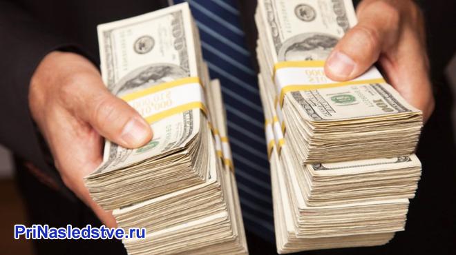 Бизнесмен держит в руках две пачки денег
