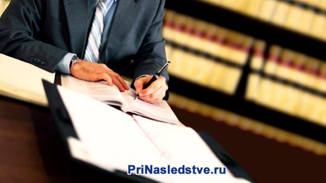 Мужчина в черной рубашке пишет конспект за столом