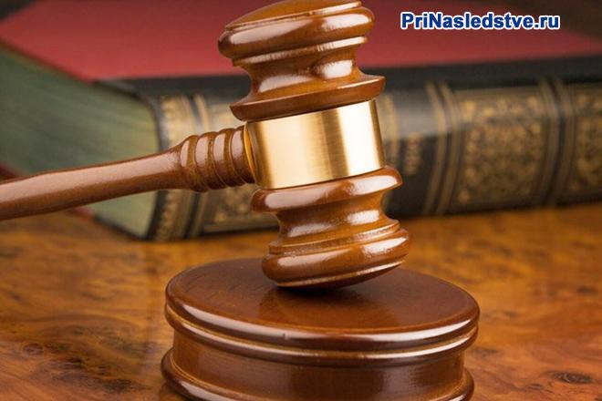 Судебный молоток и книга в красном переплете