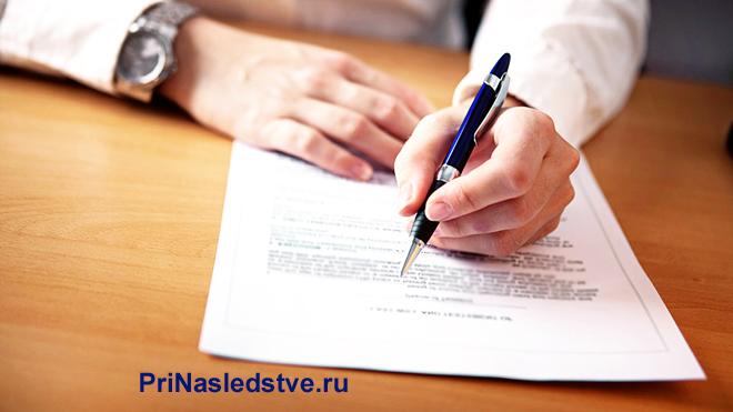 Мужчина сидит за столом и пишет синей ручкой на листе бумаги