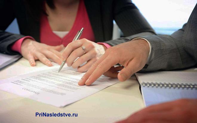 Девушка и мужчина сидят за столом и оформляют документы вместе