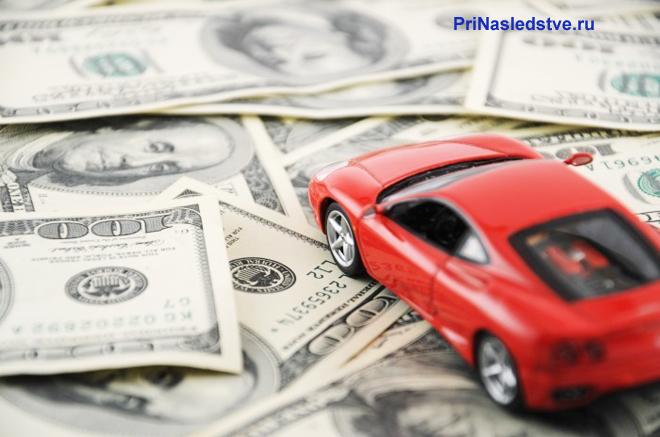 Красная машинка стоит на деньгах