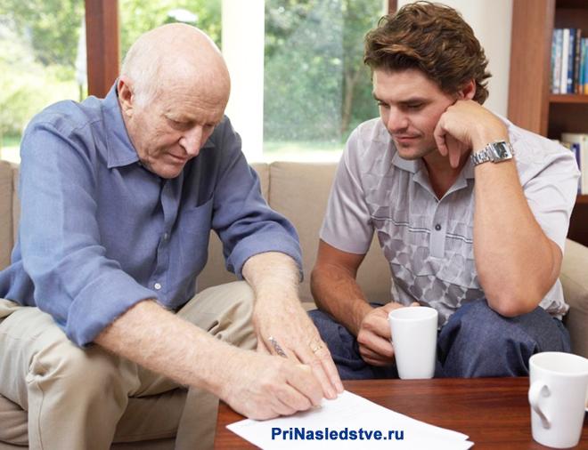 Двое мужчин сидят на диване, один из них пишет на листке бумаги