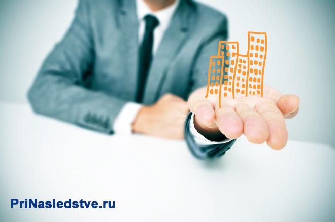 Бизнесмен держит на ладони рисунок многоэтажки
