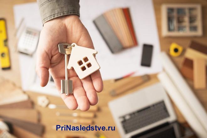 Мужчина держит на ладони ключ с брелком в виде домика