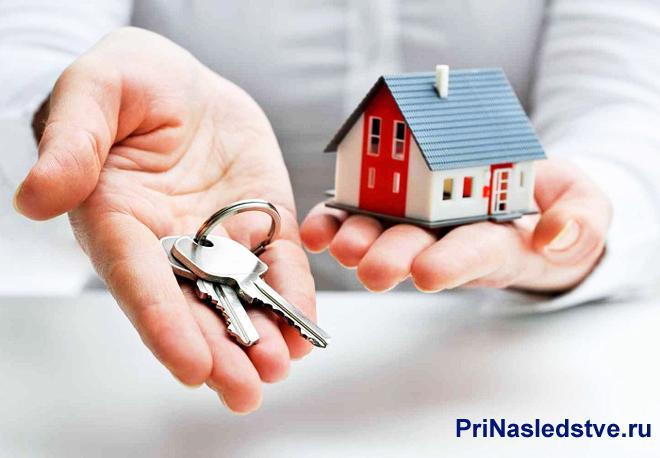 Мужчина держит в одной руке связку ключей,а в другой дом