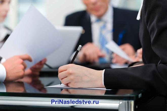 Бизнес-партнеры изучают и подписывают документы