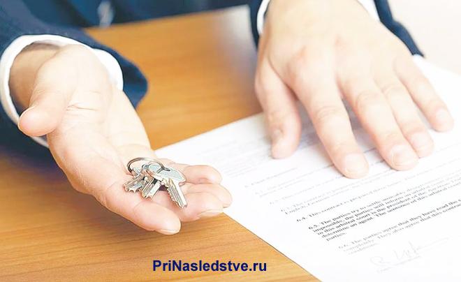 Бизнесмен сидит за столом, держит в руках ключи