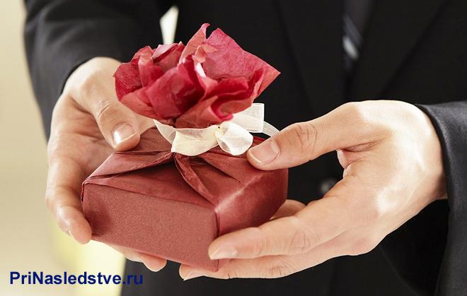Бизнесмен держит в руках подарок