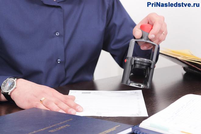 Мужчина в темной рубашке ставит печать на документе