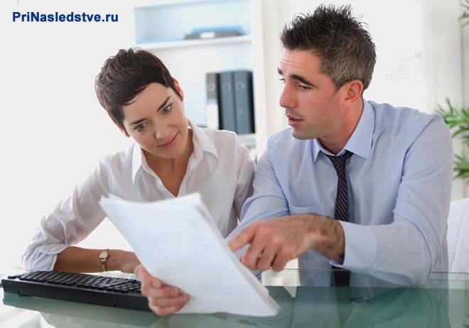 Мужчина и женщина сидят за столом и читают документы