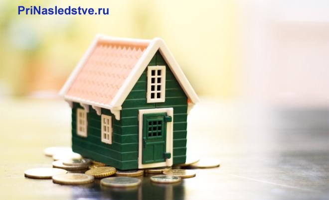 Зеленый игрушечный домик стоит на монетах